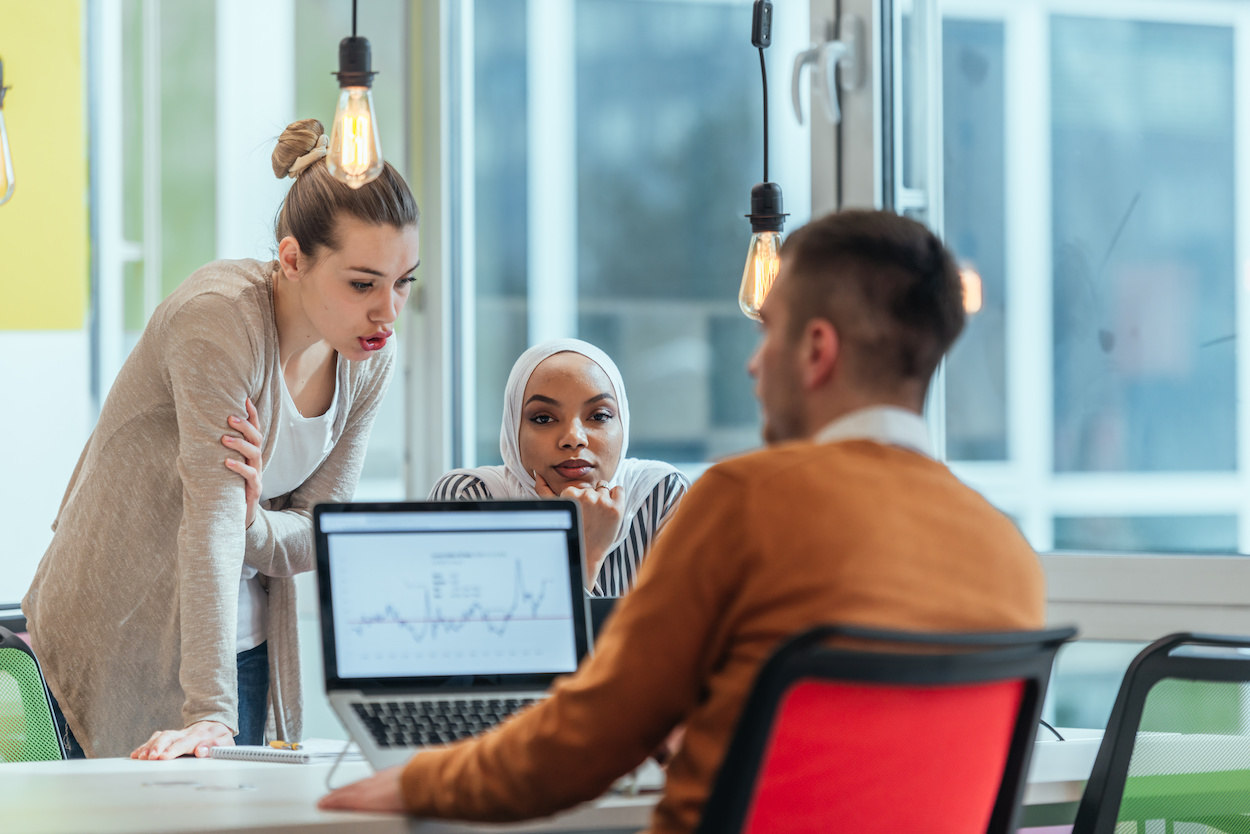 Group of coworkers, teammates helping their new African American, black, muslim colleague wearing hijab to integrate into the modern company. Multiethnic colleagues in a modern startup company.