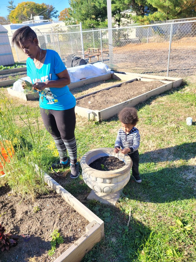 Image of African American woman and child in a garden touching dirt
